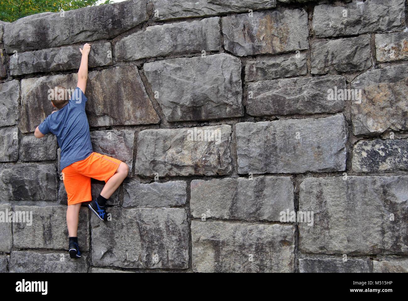 Ragazzo scalare una parete di roccia Immagini Stock