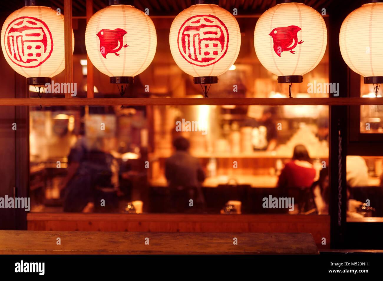 Sala da pranzo di persone all'interno di un tradizionale ristorante Giapponese con lanterne illuminata di notte. Immagini Stock