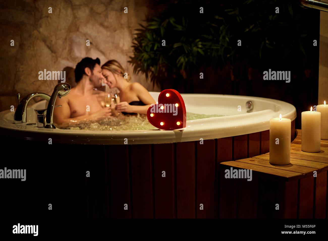 Bagno Romantico In Due cuore su uno sfondo di una coppia romantica con champagne