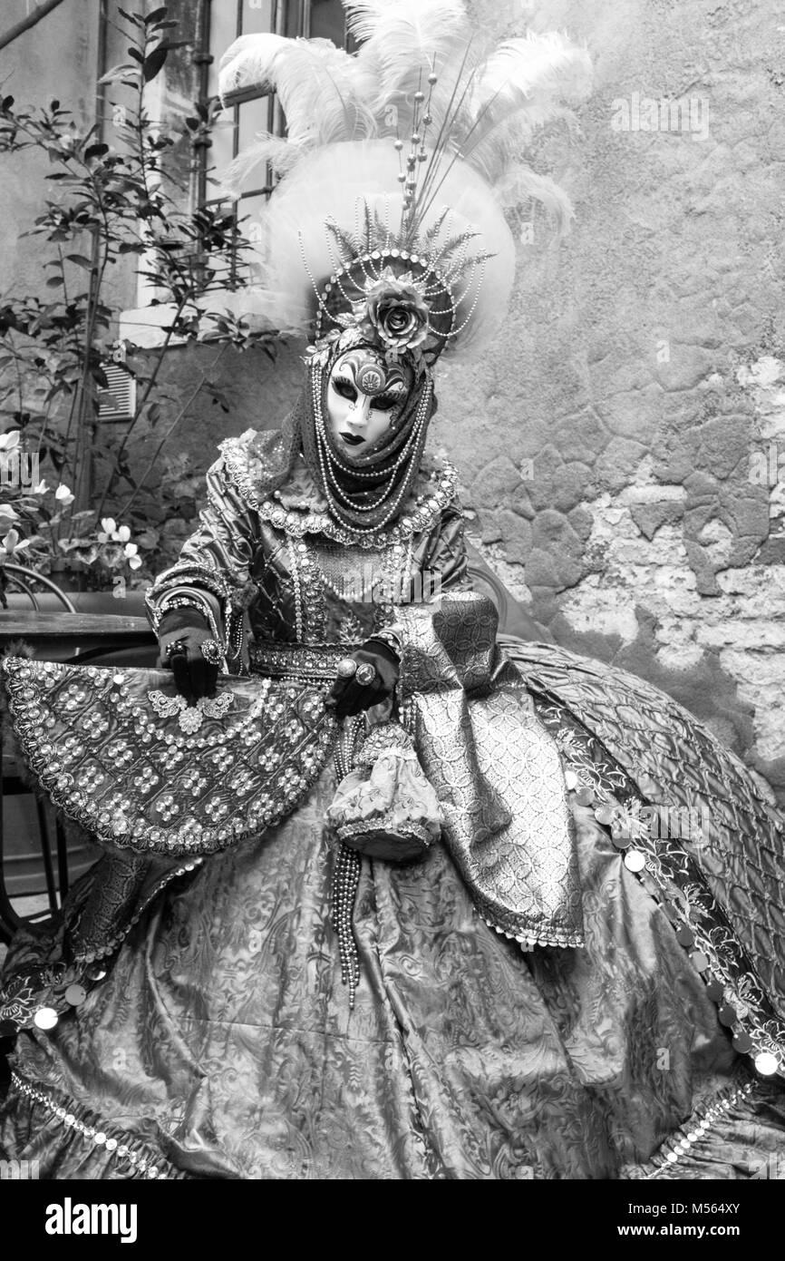 4ab8affb8e Donna mantenendo la ventola e la selvaggina di penna da indossare maschera  e costume ornati in piedi contro il vecchio muro durante il Carnevale di  Venezia ...