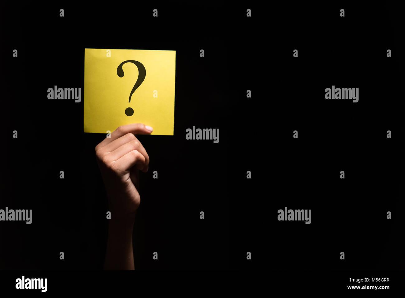 Mano che tiene un foglio giallo con punto interrogativo in uno sfondo scuro Immagini Stock