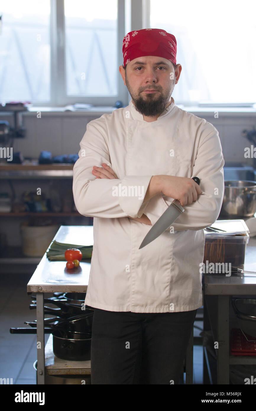 Ritratto di un quartiere alla moda di chef in bandana tenendo un coltello in una cucina Immagini Stock
