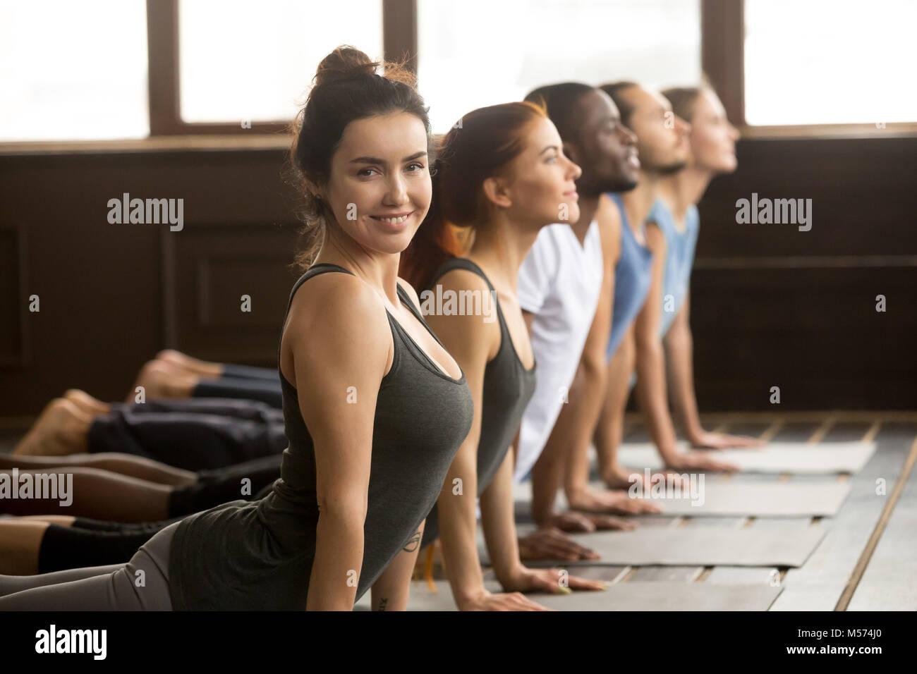 Istruttore Yoga guardando la fotocamera facendo esercizio in gruppo traini Immagini Stock
