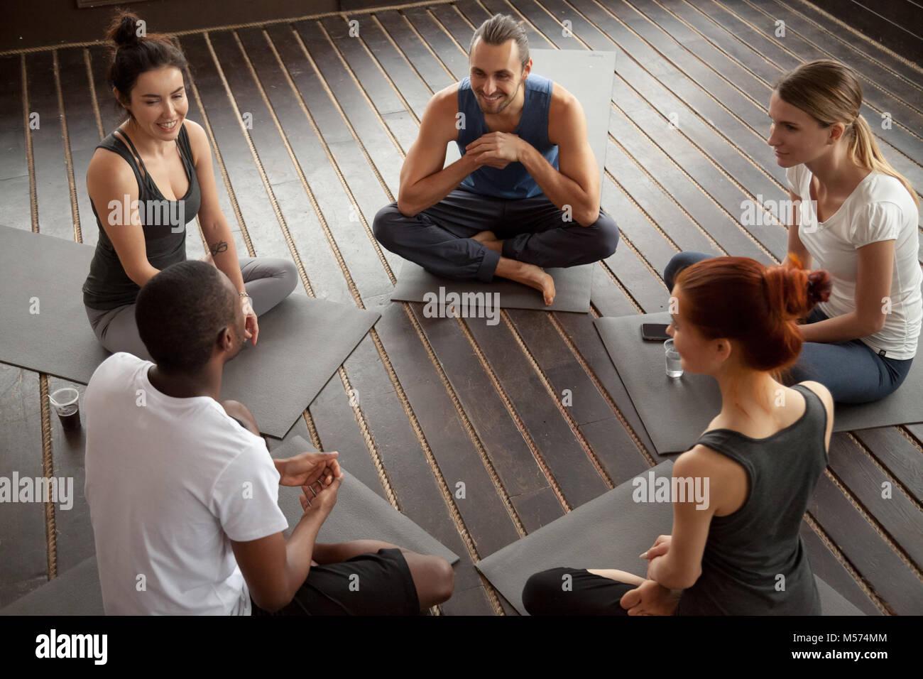 Diverse persone sorridenti seduti sulle stuoie di parlare prima del treno di yoga Immagini Stock