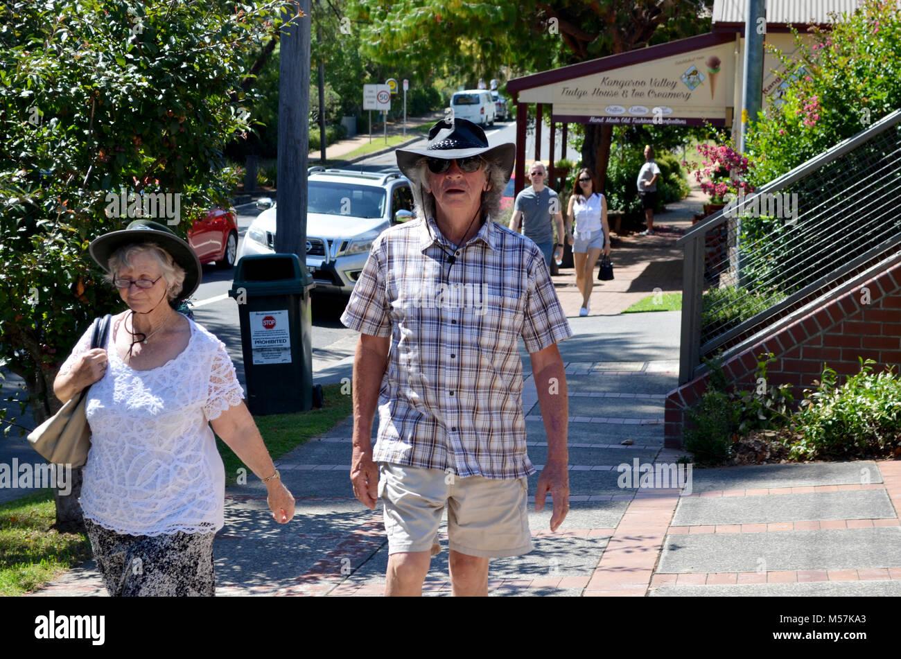 Coppia di anziani di indossare cappelli a piedi nella strada di Kangaroo Valley NSW Australia Immagini Stock