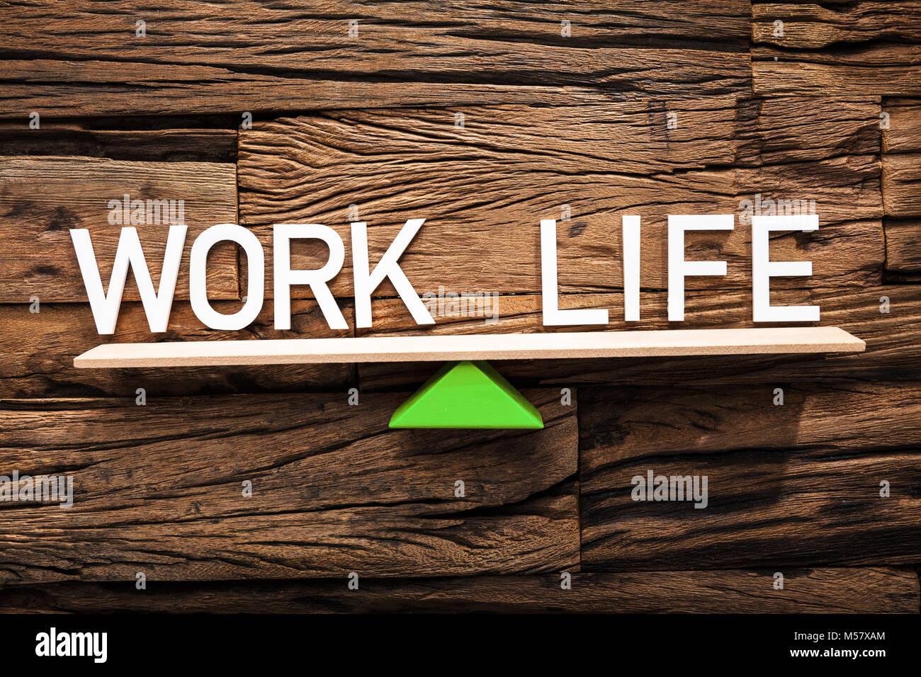 Primo piano del testo di lavoro e di vita in equilibrio su altalena contro il legno Immagini Stock