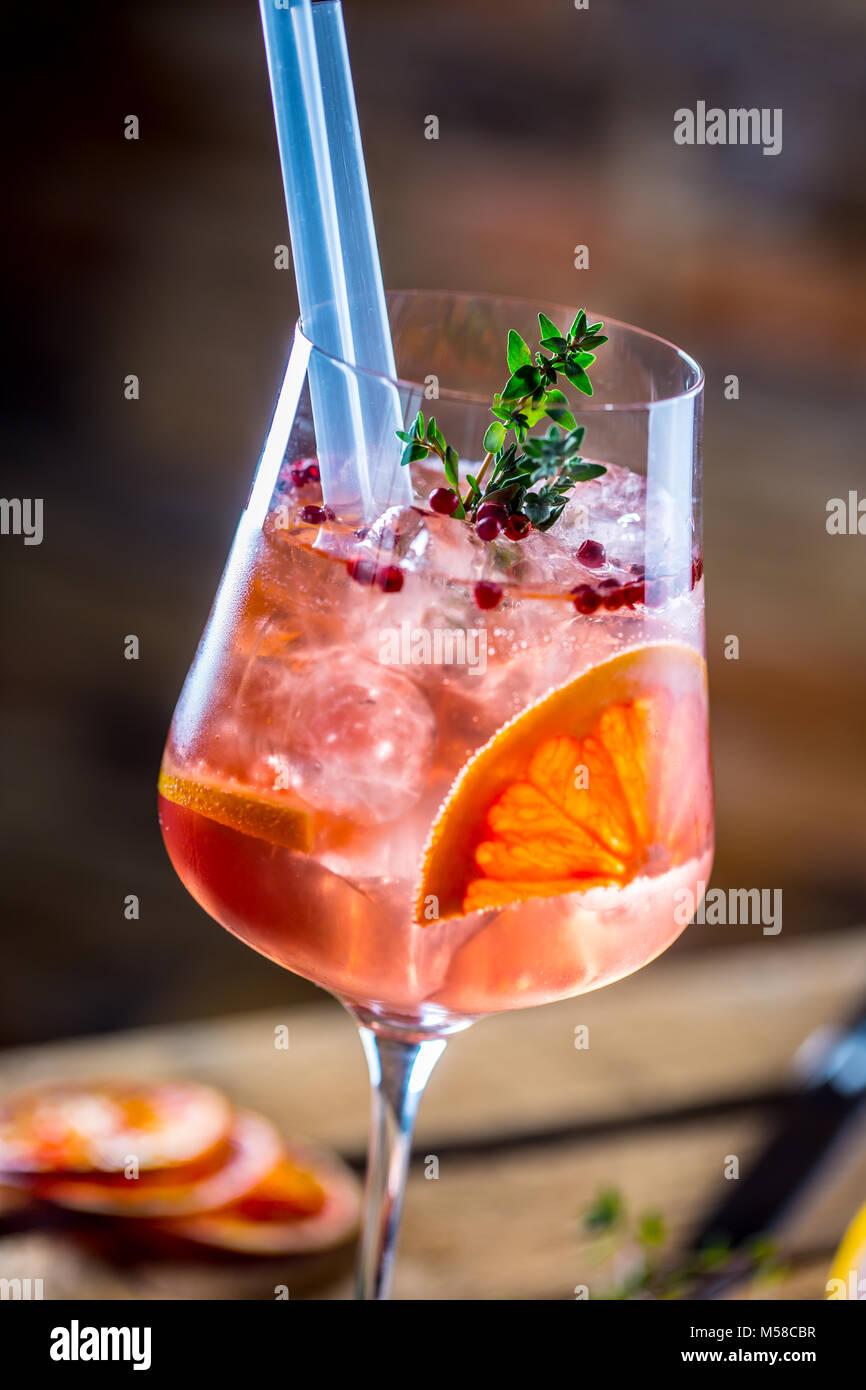 Cocktail di benvenuto su una vecchia tavola di legno. Bevanda alcolica con frutti tropicali pepe rosso di erbe e Immagini Stock