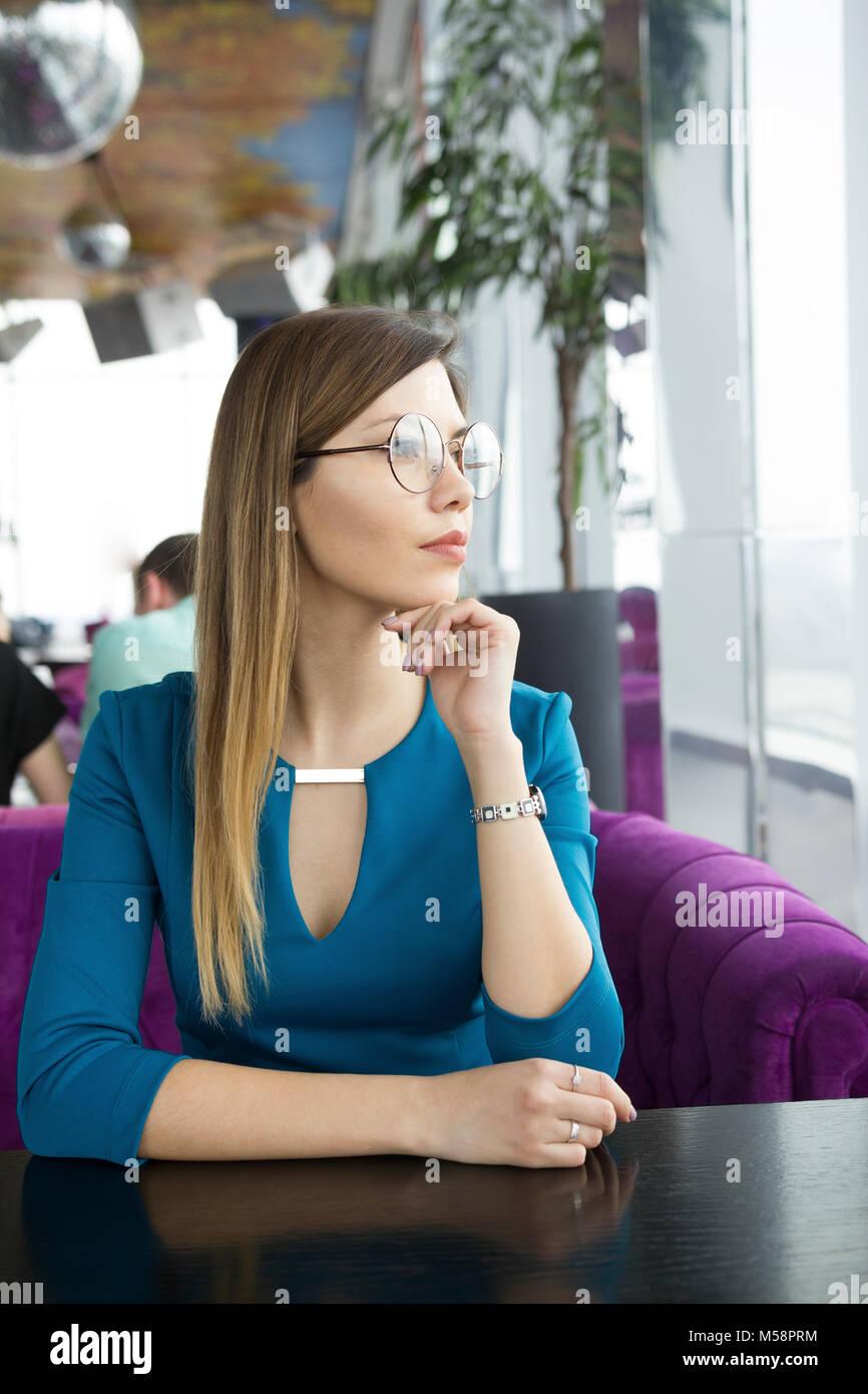 Bellissima ragazza con gli occhiali seduto in un bar Immagini Stock