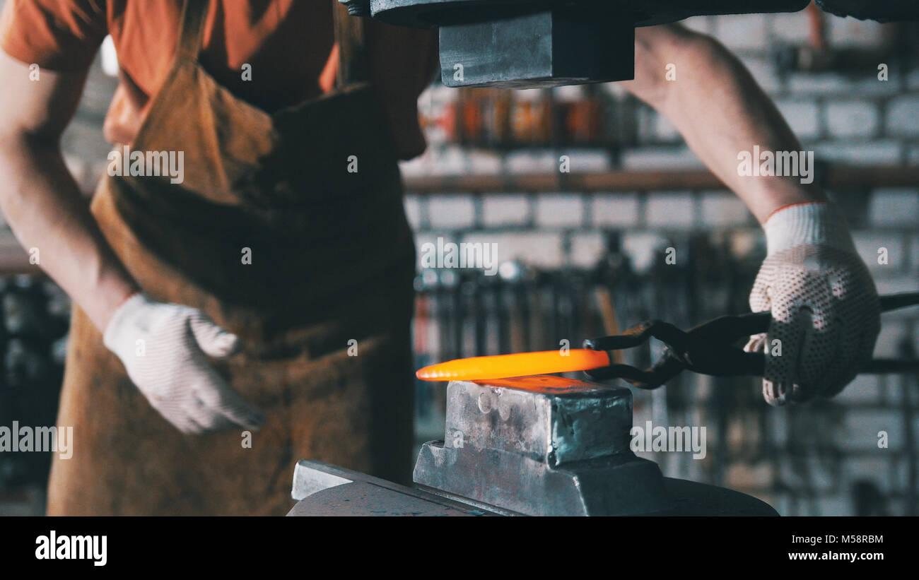 Automatico di martellatura meccanica - fabbro rosso di forgiatura ferro caldo sull'incudine, teleobiettivo Immagini Stock