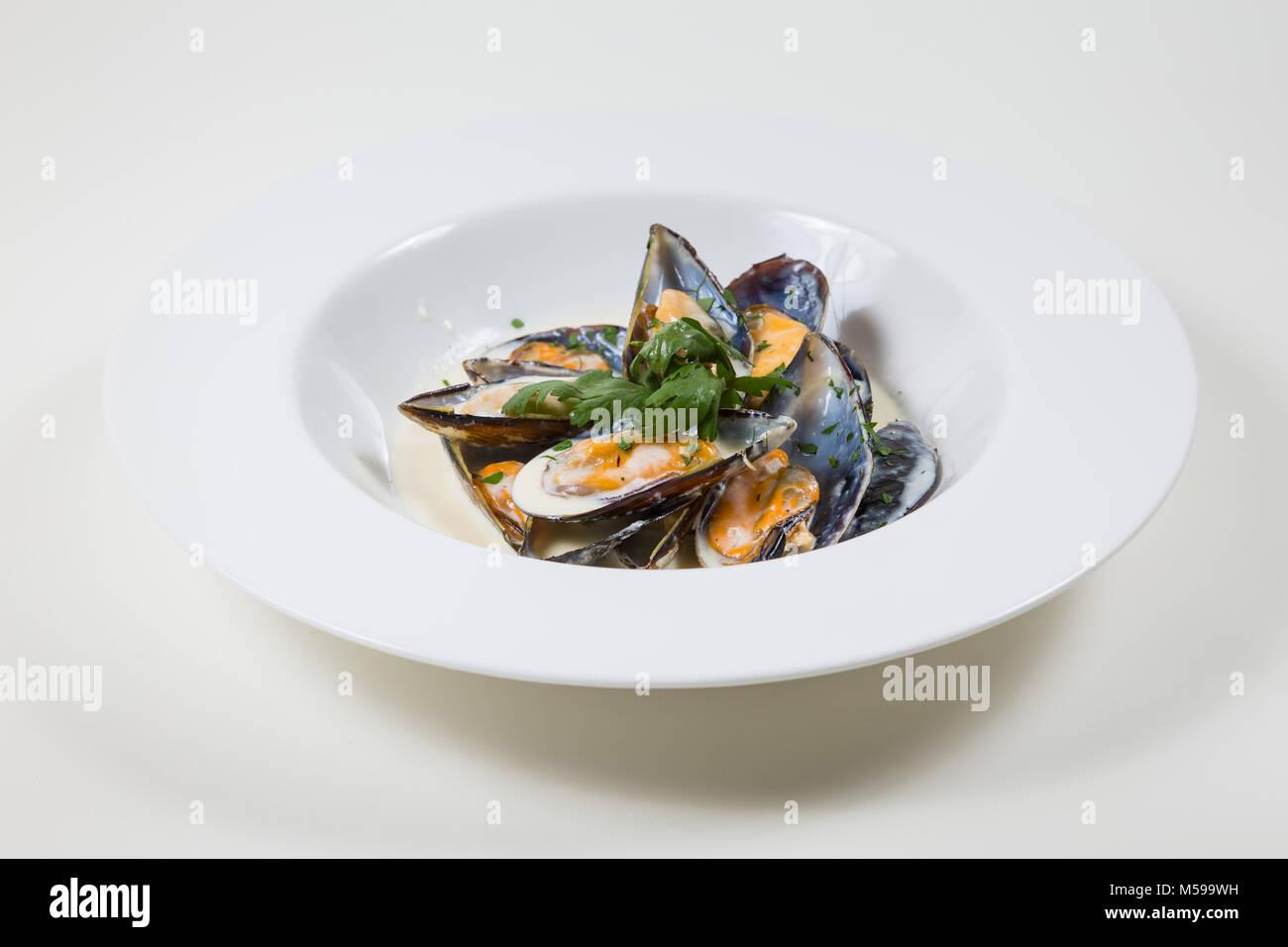 Le cozze in una salsa cremosa in una ciotola bianco su sfondo bianco isolato Foto Stock