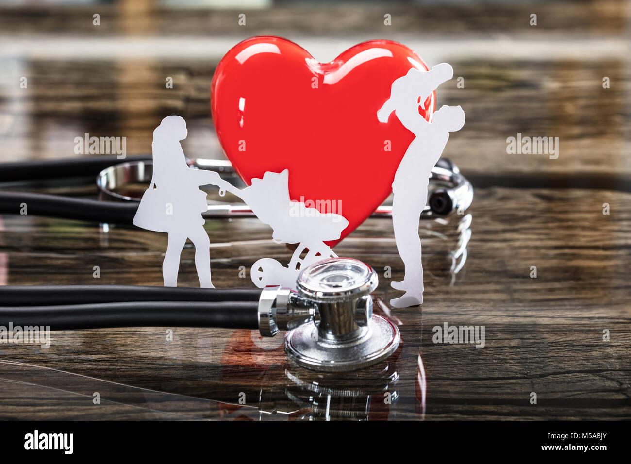 Close-up della famiglia tagliati fuori e cuore rosso con uno stetoscopio sulla scrivania Immagini Stock