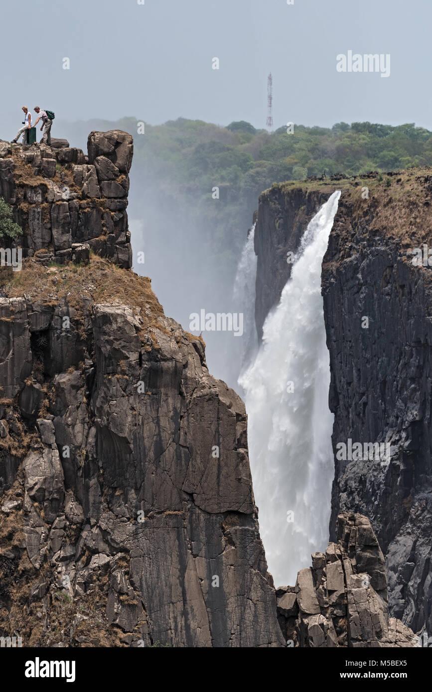 I turisti a Victoria Falls, Zimbabwe, Zambia, Africa Immagini Stock