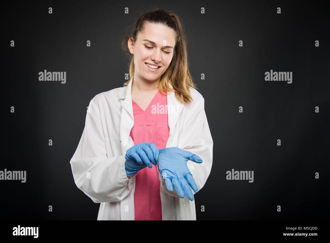 Giovani donne medico ritratto prendendo i suoi guanti sterili su sfondo nero con copyspace area pubblicitaria Foto Stock