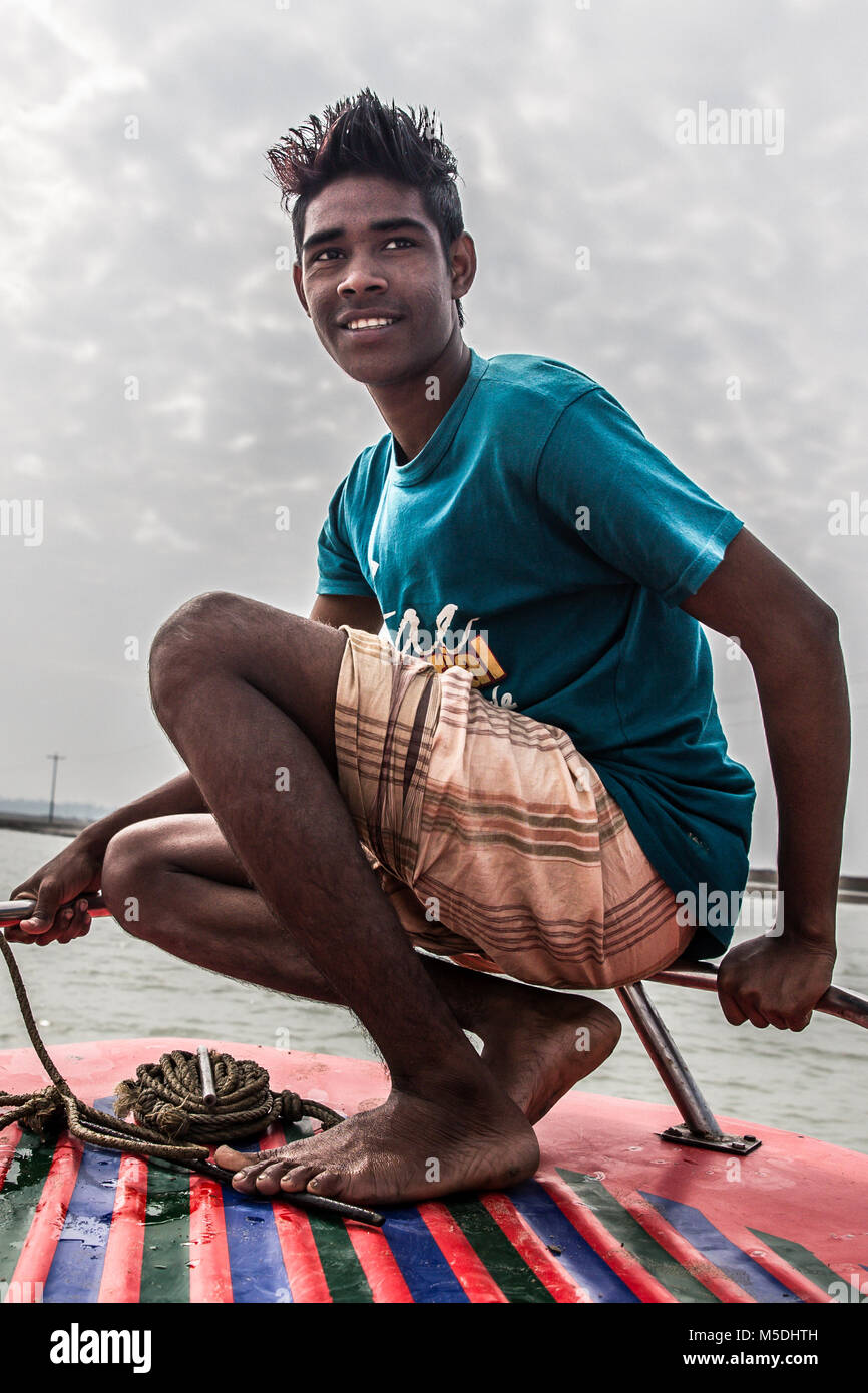 Febbraio 22, 2018 - Cox's Bazar, Bangladesh - un giovane uomo bengalese pone per la telecamera su una barca vicino Foto Stock