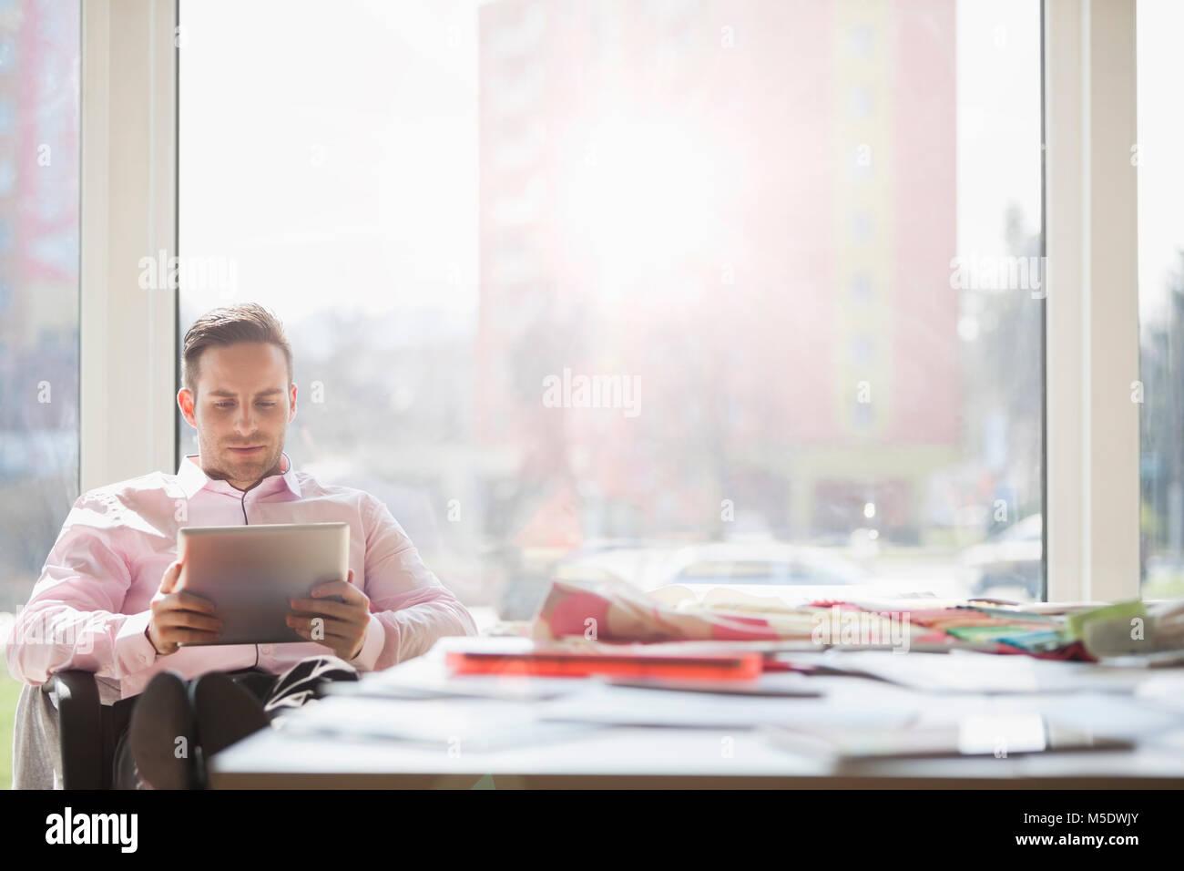 Giovane impreditore con tavoletta digitale a un tavolo per conferenza in ufficio creativo Immagini Stock