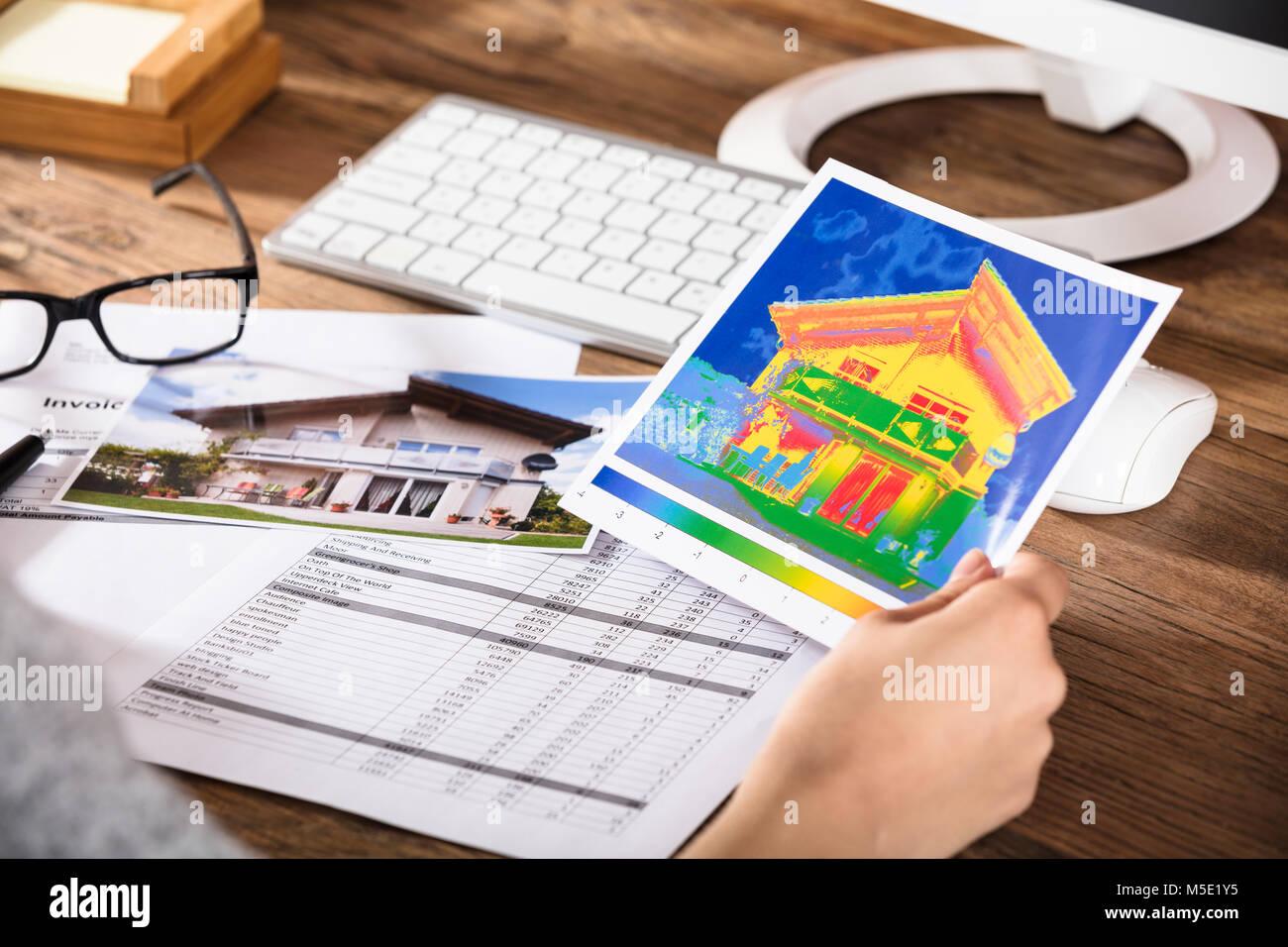 Close-up di una persona analizzando l'immagine termica di una casa sulla scrivania Immagini Stock