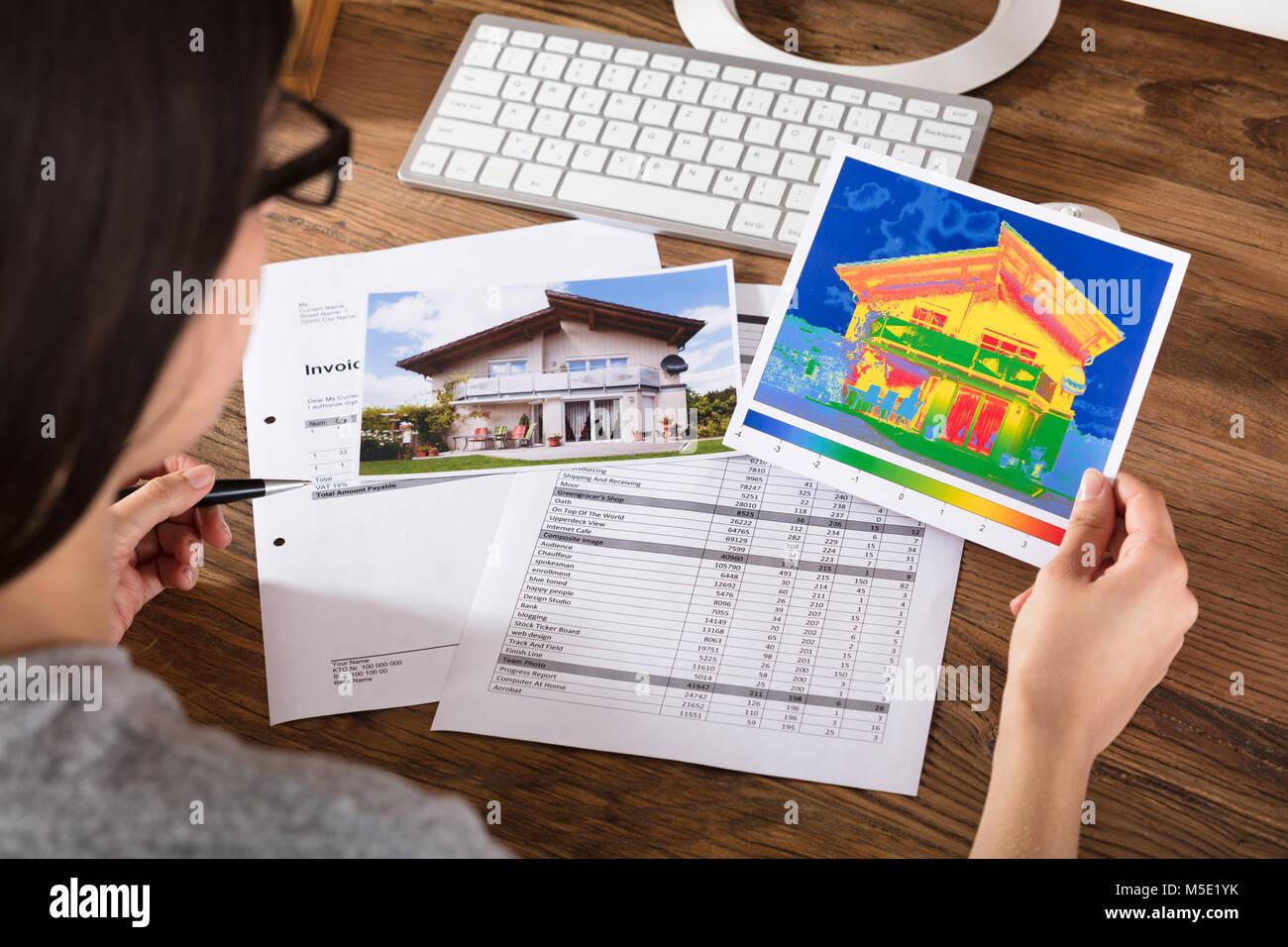 Close-up di una persona analizzando la perdita di calore e l'efficienza energetica di una casa Immagini Stock