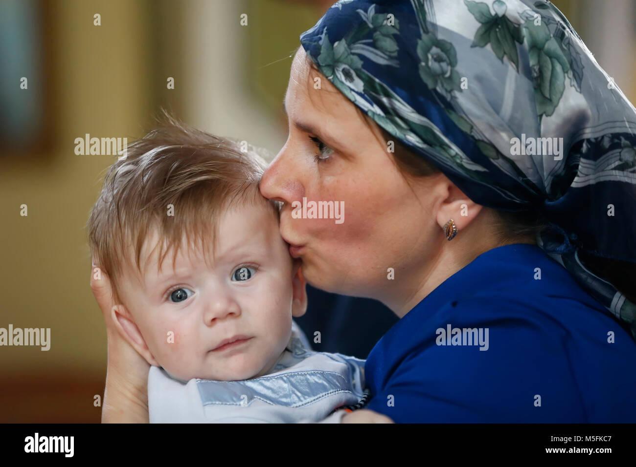 La Bielorussia, la città di Gomel, San Nicola Monastero.11 Giugno 2016.Il battesimo del bambino.Una madre bacia Immagini Stock