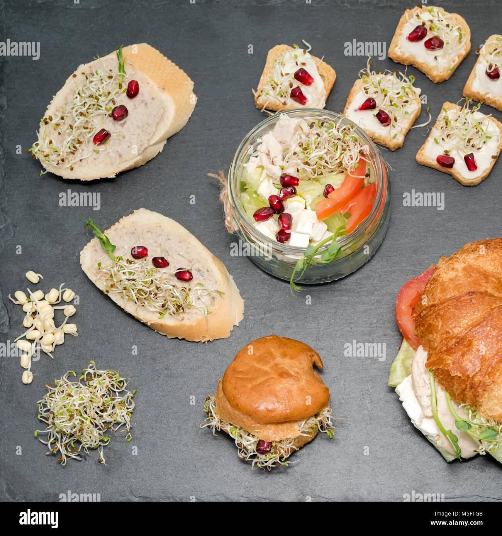 Cibo sano, menu con microgreens. Sandwich vegetariano con micro verdi assortimento. Partito vegano tabella degli Immagini Stock