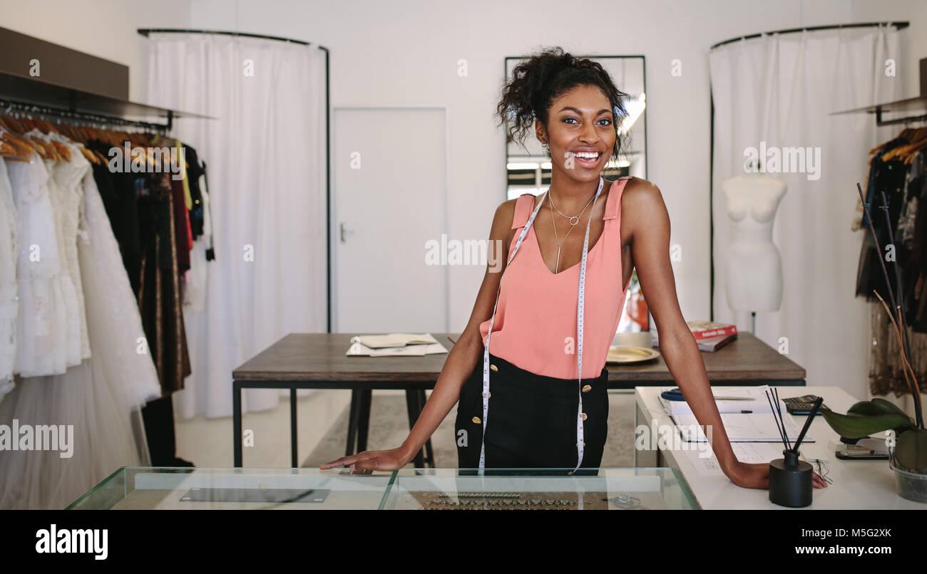 92b029bd8b2b Femmina designer di moda in piedi alla sua scrivania nella sua boutique.  Abito femminile designer nel suo negozio di tessuto con un nastro di  misurazione ...