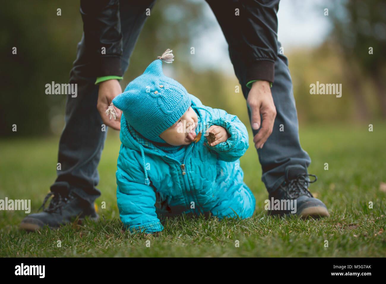 La famiglia felice camminando in autunno parco: il bambino cerca di gusto che non può provare Immagini Stock