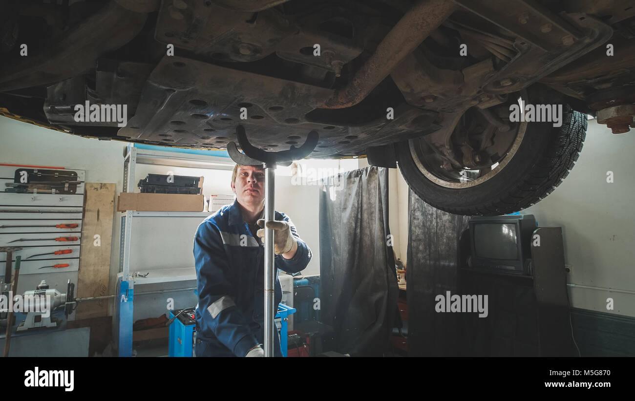 Meccanico al lavoro - automobile del fondo sotto sollevato in auto Immagini Stock