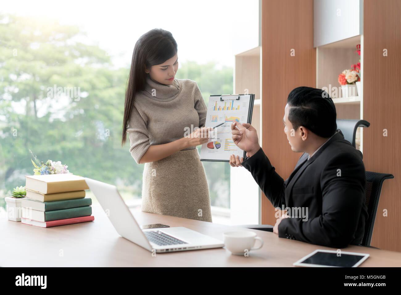 Felice asian imprenditrice presentando pila grafico per manager in ufficio. Presentazione aziendale e concetto di incontro. Foto Stock