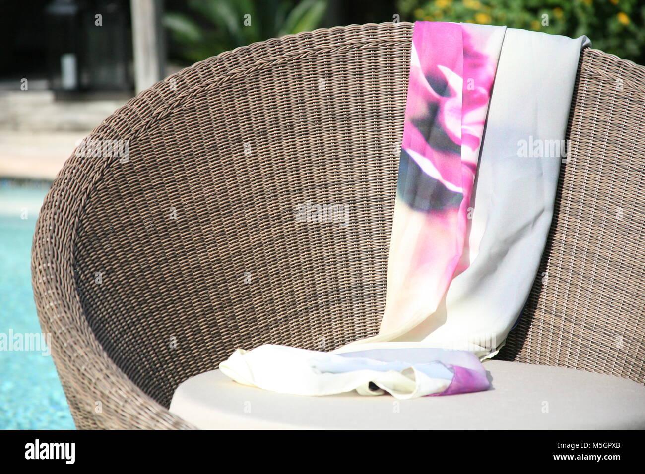 Curva sedia in vimini dalla piscina con motivi floreali rosa sarong drappeggiato sopra di esso Immagini Stock