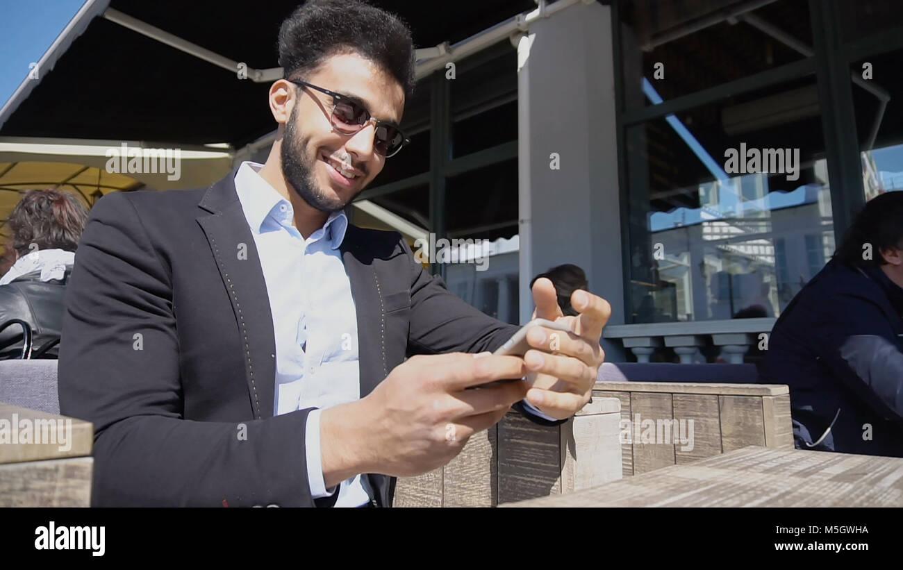 Un ragazzo italiano raccontare barzellette alla moglie dal telefono. Immagini Stock