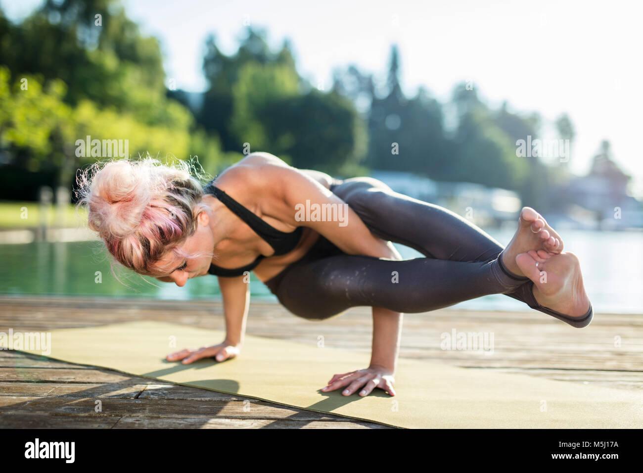 La donna a praticare yoga sul pontile di un lago Immagini Stock