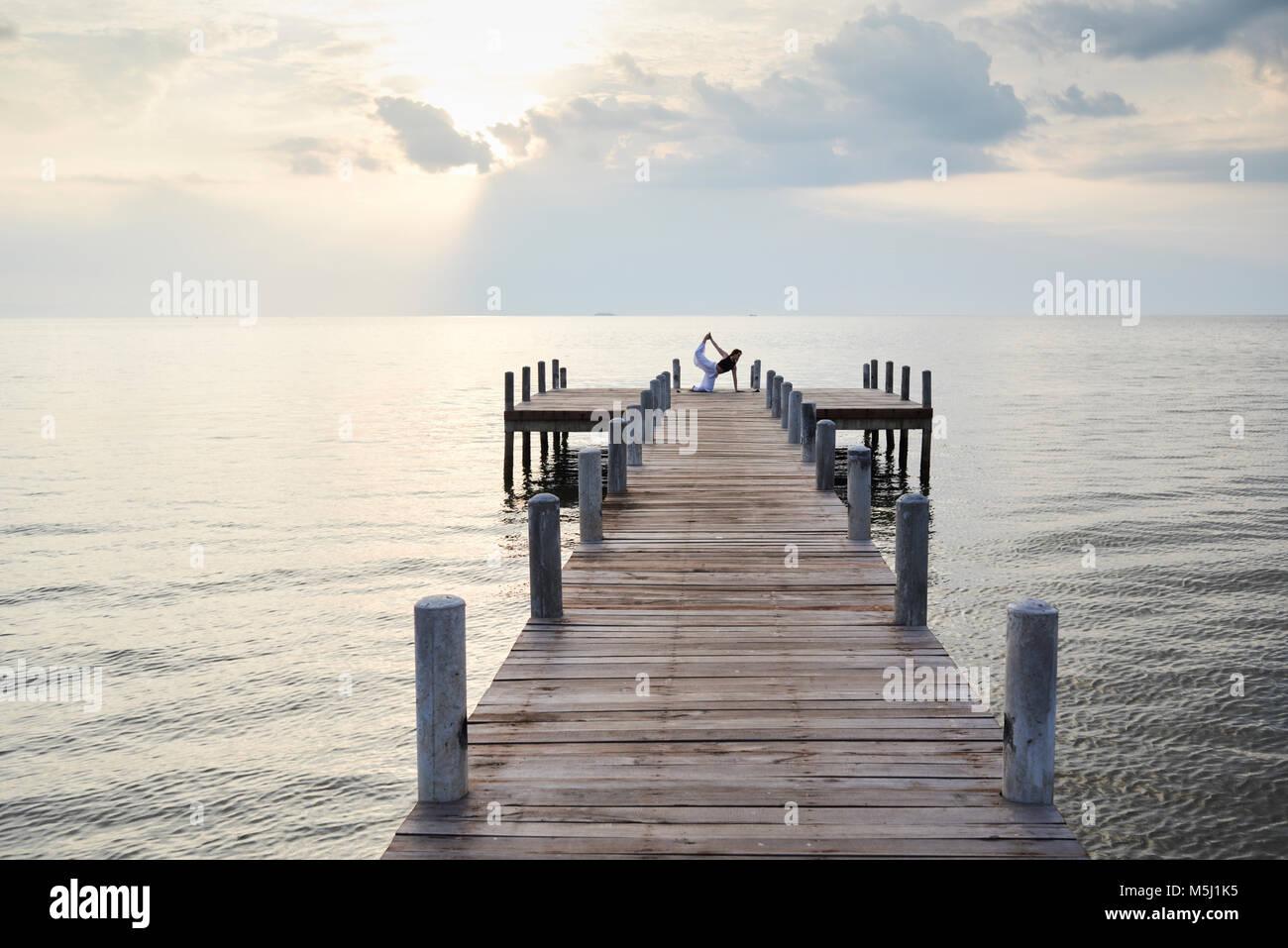 Istruttore Yoga in bird dog posizione contro il tramonto e il mare. Kep, Cambogia. Foto Stock
