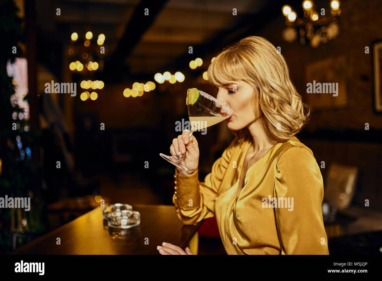 Donna elegante bere un cocktail in un bar Immagini Stock