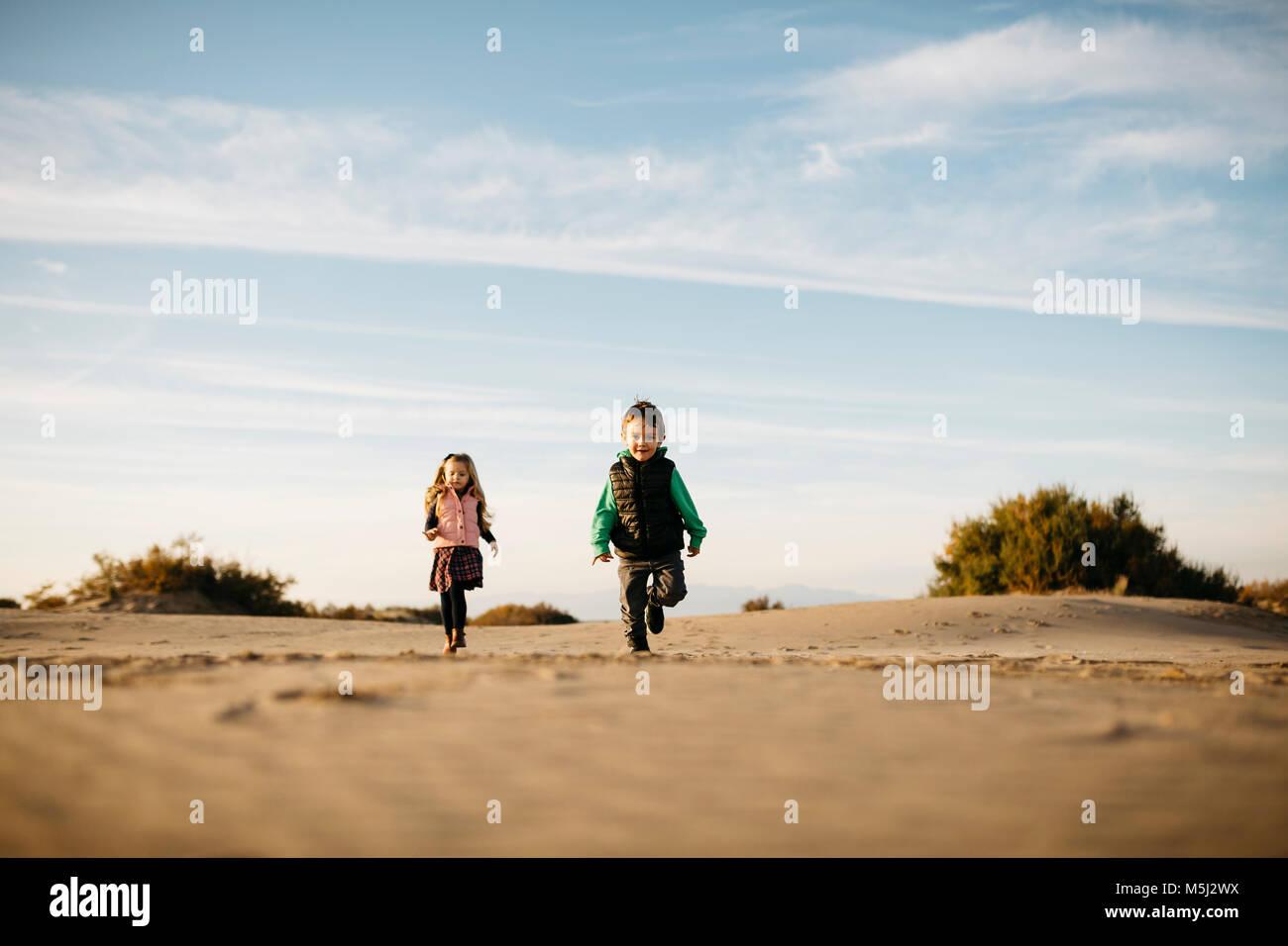 Due bambini di correre sulla spiaggia in inverno Immagini Stock