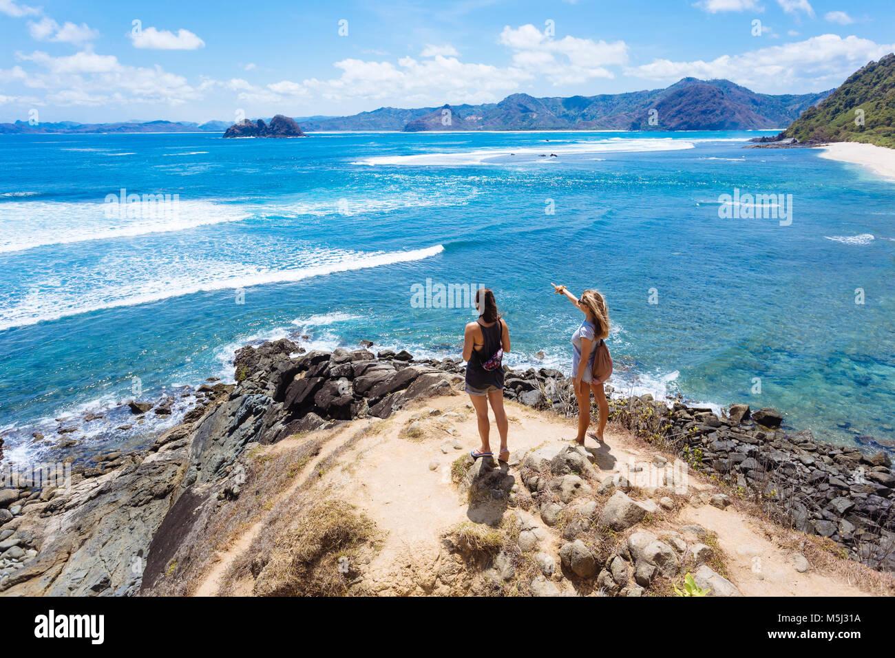 Indonesia, Lombok, due giovani donne a fascia costiera sull'oceano Foto Stock