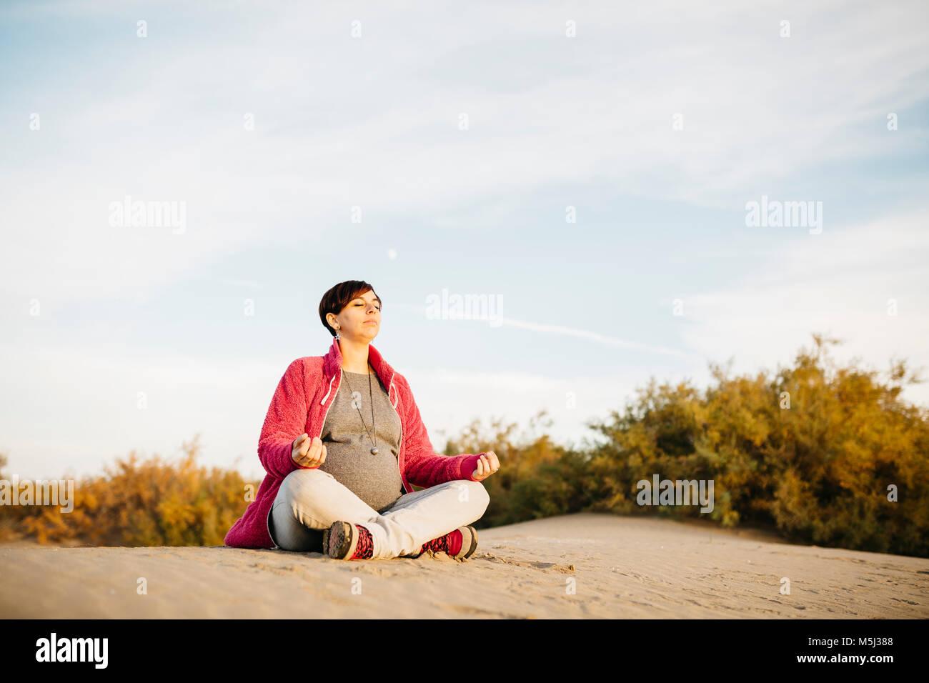 Donna incinta a praticare yoga sulla spiaggia in inverno Immagini Stock