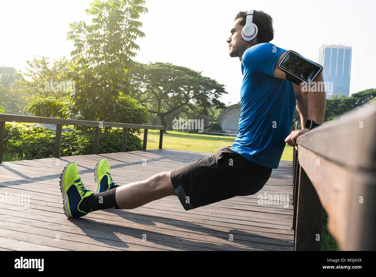 Runner con cuffie facendo push-up nel parco urbano Immagini Stock