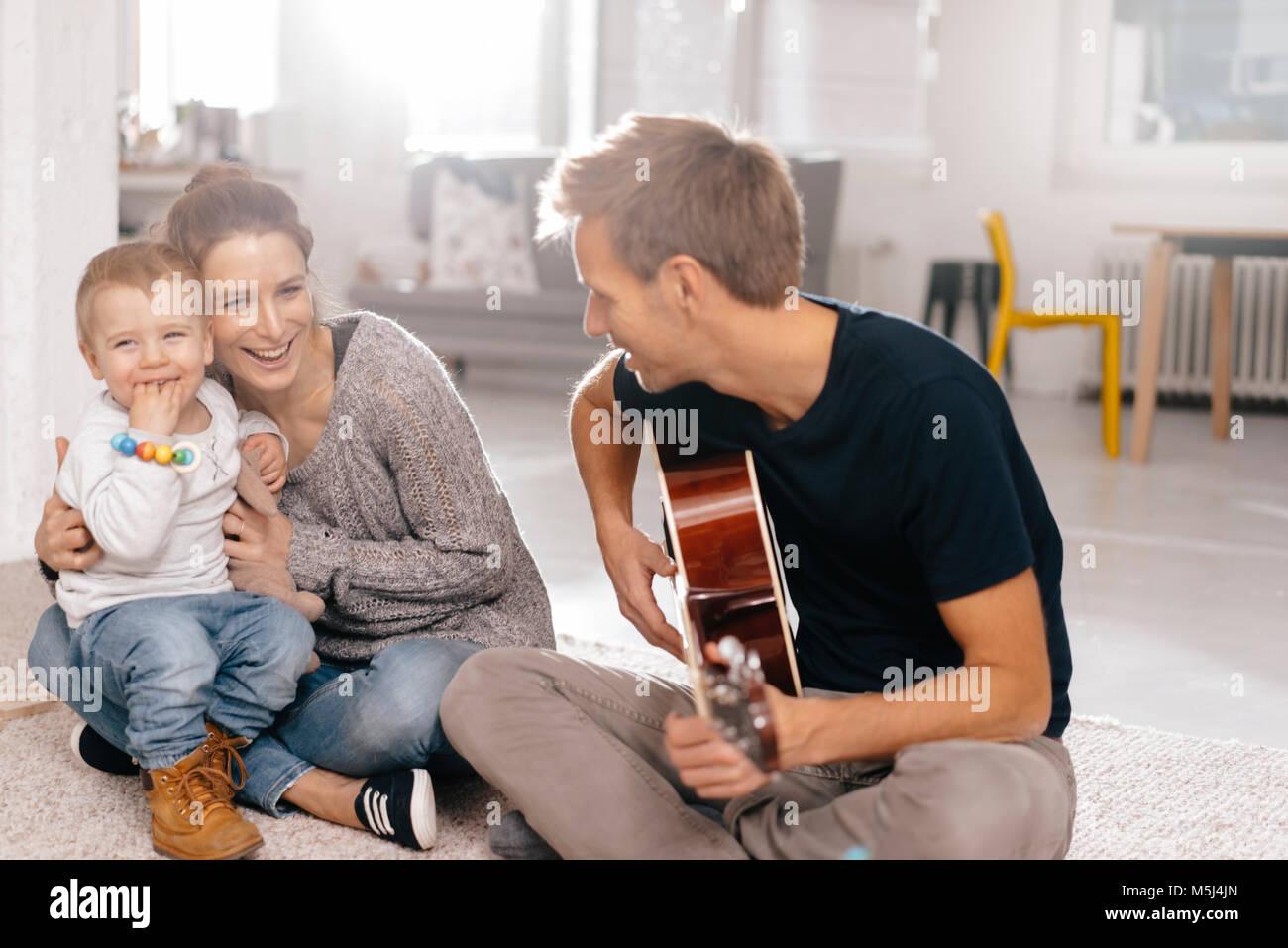 La famiglia felice seduto sul pavimento con il padre a suonare la chitarra Immagini Stock