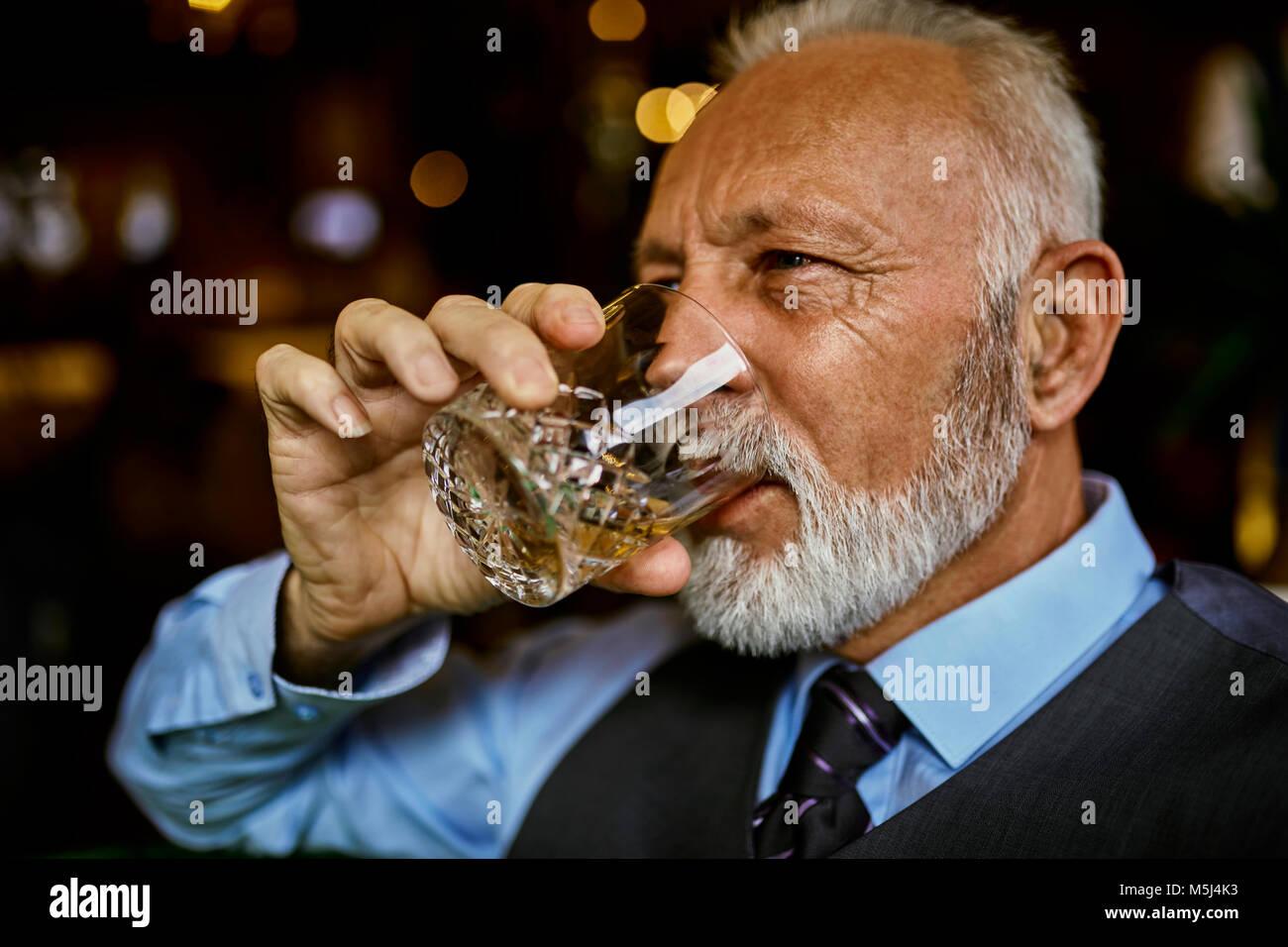 Ritratto di elegante uomo senior di bere dal bicchiere Immagini Stock