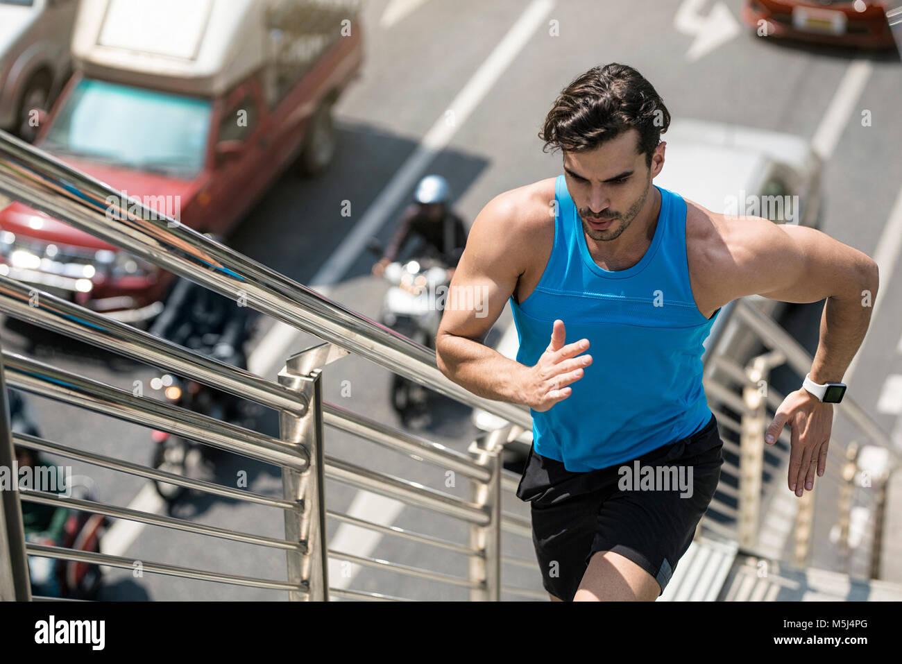 Uomo in blu maglietta fitness in esecuzione al piano di sopra in città Immagini Stock