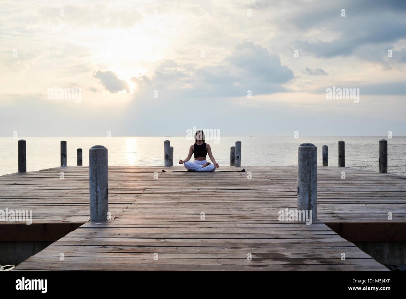 Istruttore Yoga pratica di meditazione in una posizione del loto contro il tramonto e il mare. Kep, Cambogia. Immagini Stock