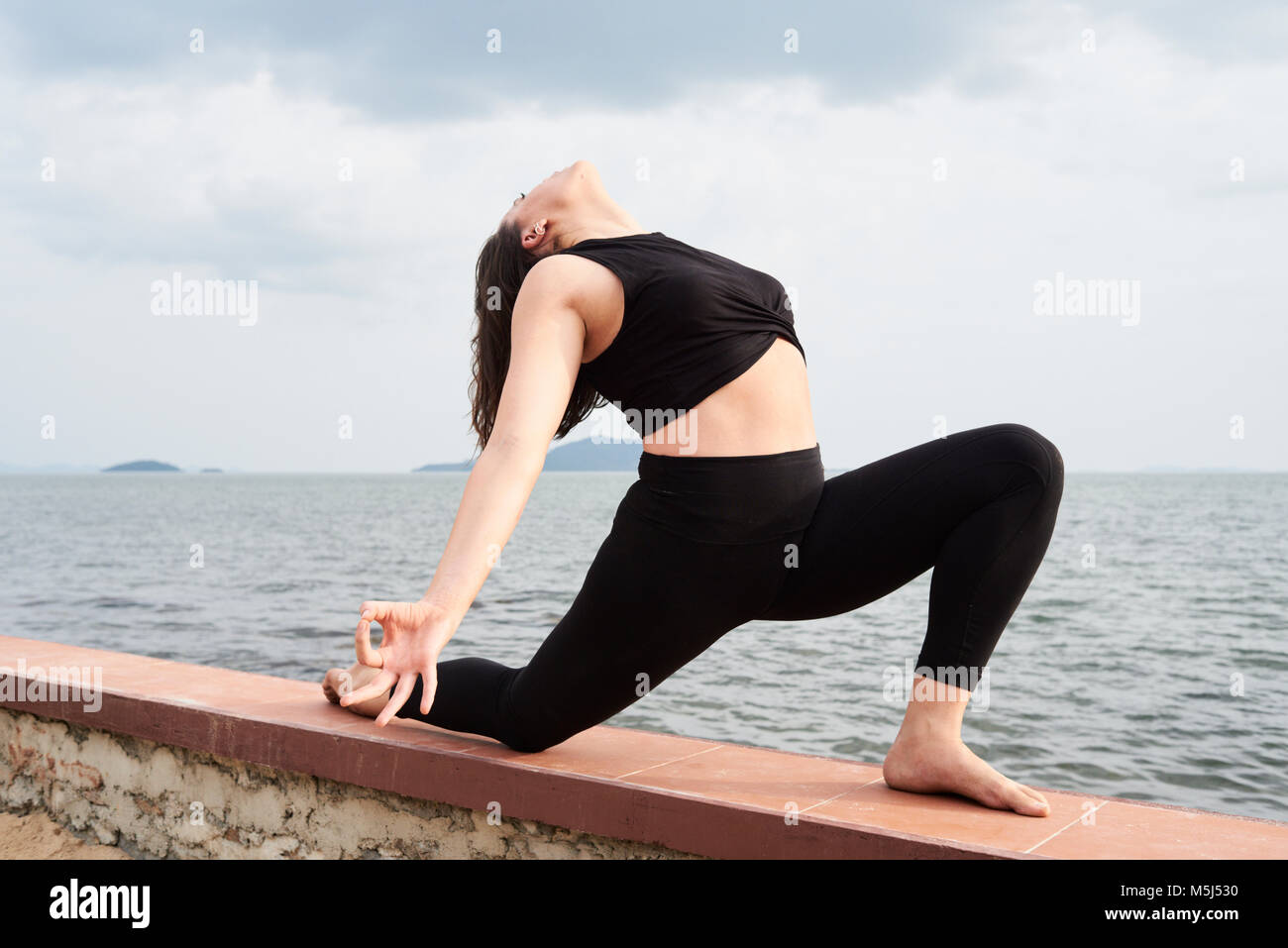 Istruttore Yoga nella posizione del Guerriero con le braccia aperte e a faccia in su una recinzione accanto al mare. Immagini Stock