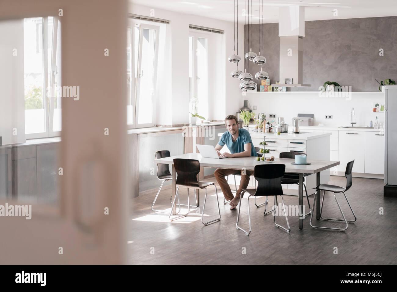 Uomo seduto al tavolo in cucina a lavorare sul computer ...