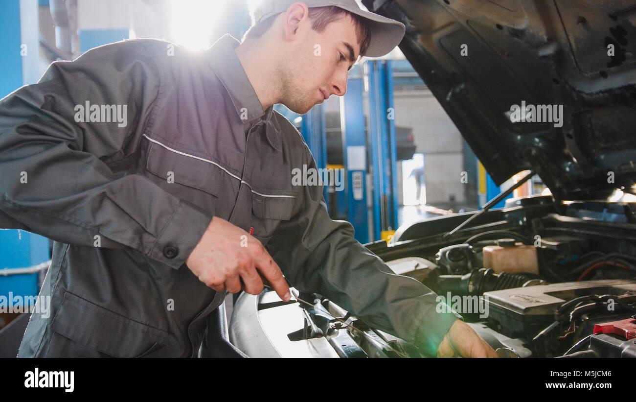 Il meccanico in tuta controlla il livello dell'olio motore in auto - Servizio automobile riparazione Immagini Stock