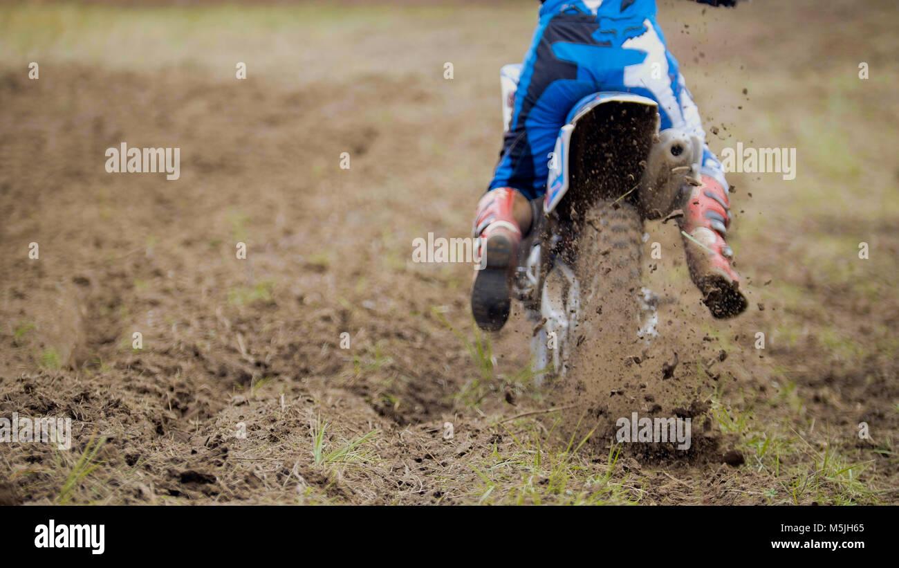 Motocross racer start in sella alla sua sporcizia Cross MX bike sollevando la polvere vista posteriore, chiudere Immagini Stock