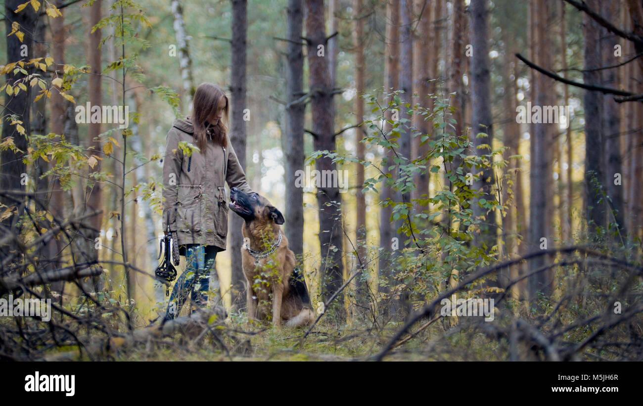 Giovane bella femmina modello giocando con il suo animale domestico - pastore tedesco - a piedi su una foresta di Immagini Stock