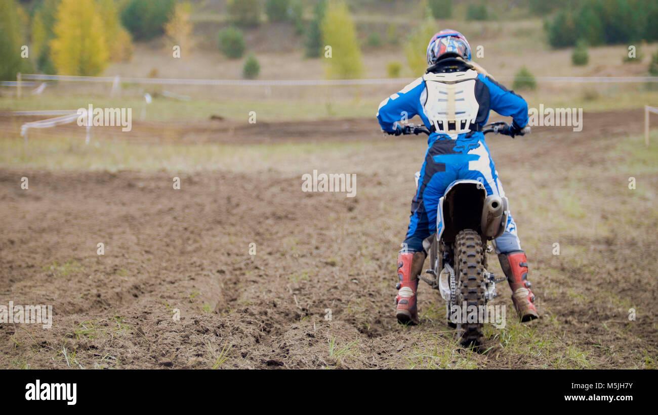 Motocross racer start in sella alla sua sporcizia Cross MX Bike - Vista posteriore Immagini Stock