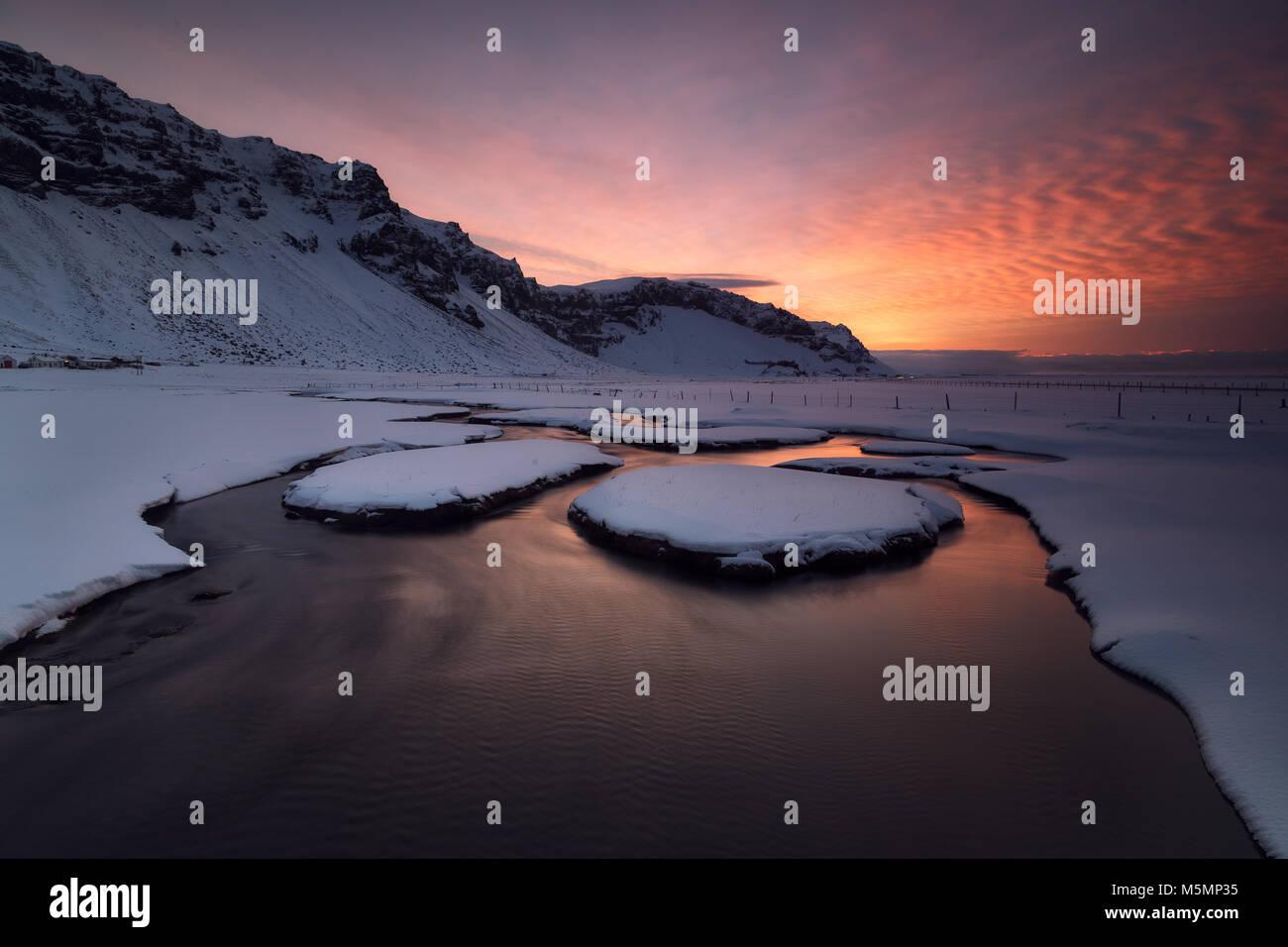 Tramonto su un fiume nevicato in Islanda Immagini Stock