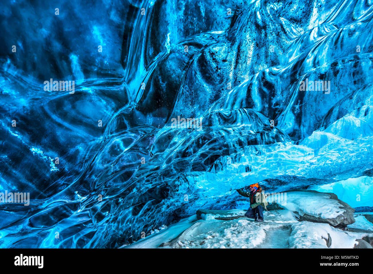 Turisti alla scoperta della grotta di ghiaccio, active traveler uomo godendo la bellezza di una grotta glaciale, Immagini Stock