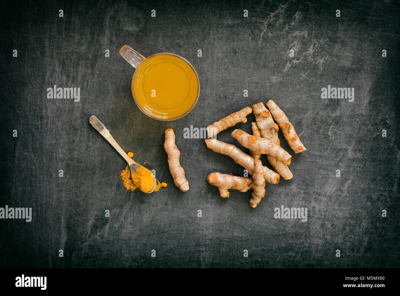 Curcuma longa. Curcuma tè con polvere e rizomi su un sfondo di ardesia. Immagini Stock