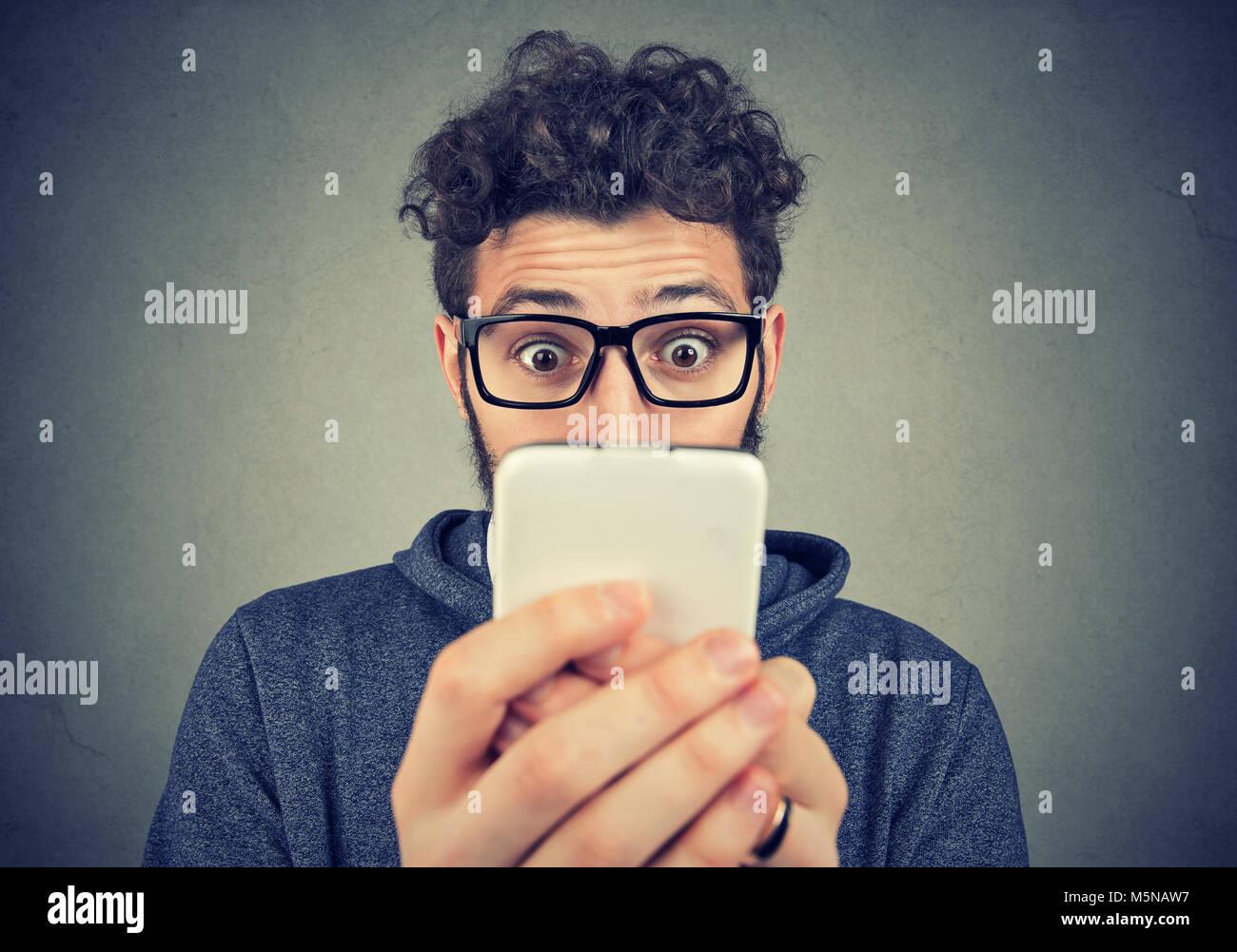 Giovane uomo barbuto in bicchieri usando il telefono con espressione di grande stupore. Immagini Stock